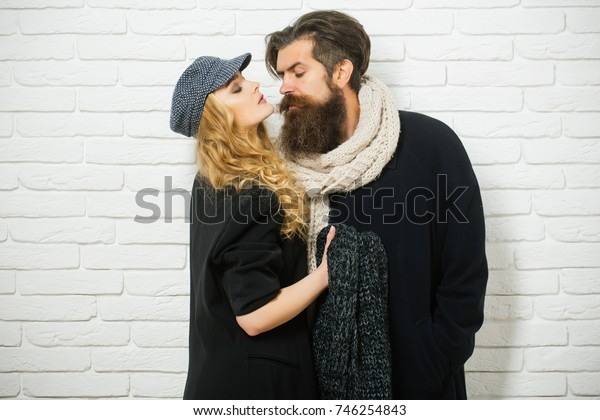 Love and romance. Couple in love of fashionable man and woman. Man with beard and girl with long hair. Relations of girl and guy in autumn. Boyfriend and girlfriend on brick wall background.
