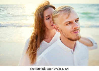 Love and romance. Honeymoon on the sea shore. Beautiful loving couple in white cloth embracing on the beach.