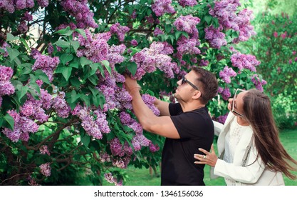 Love and romance, relationship, happy couple. Beautiful nature scene with blooming lilac tree. Sunny day. Spring flowers.