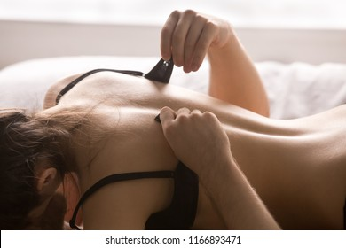 Love, romance, sex concept. Boyfriend unfasten girlfriend bra during foreplay before making love, couple undressing, man unzip lover lingerie enjoying intimacy before sex, woman on top. Close up view