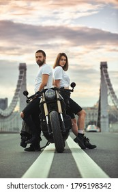 Love and romantic concept. Beautiful couple on motorcycle stands opposite each other in the middle of the road on the bridge, on double solid