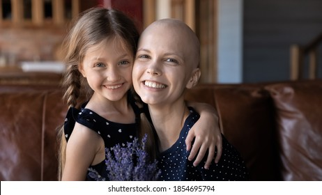 Love saving life. Cheerful affectionate millennial mom having cancer diagnosis posing for portrait on sofa in living room at home getting flowers on Women Day looking at camera cuddling small daughter