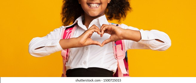 Love School. Black Elementary Schoolgirl Showing Heart Shape Gesture With Fingers On Yellow Studio Background. Cropped, Panorama