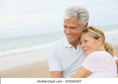 In love senior couple embracing at the beach