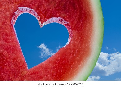 Love shape cut into juicy watermelon on blue sky