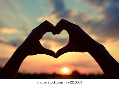 Love shape hand or Heart shaped silhouette at sunset background