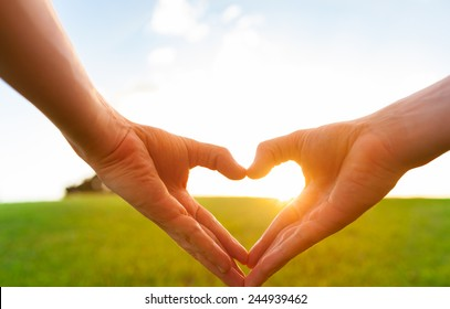 Love shape hands against natural sunset background