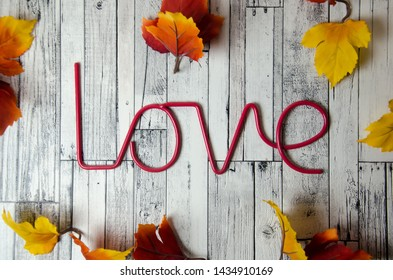 Love sign with autumn leaves. Wooden background