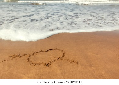 Love sign (heart with an arrow) written on sand with ocean waves flowing