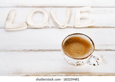 LOVE sign letters with espresso coffee in white cup,  old rustic  style table, shallow dof