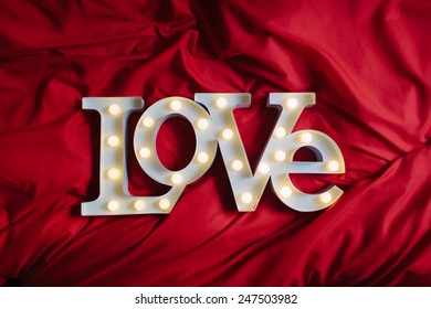 Love Sign Text Over a Red Bed Blanket