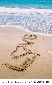 'Love' signature on the beach sand