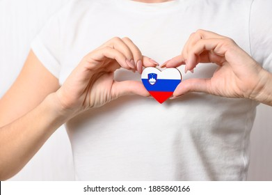 Love Slovenia. A girl holds a heart in the form of the flag of Slovenia on her chest. Slovenian concept of patriotism
