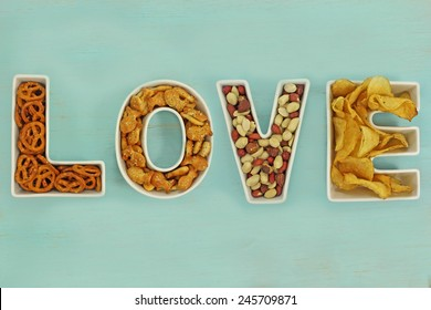 Love snacks in Love letter bowls on a distressed duck egg blue wooden background.