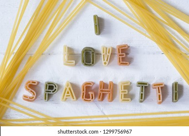 I love spaghetti text written with pasta letters font on white wooden background