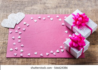 Love and still life concept. Valentines day holiday gift card and box on a rustic wooden table. Copy space background