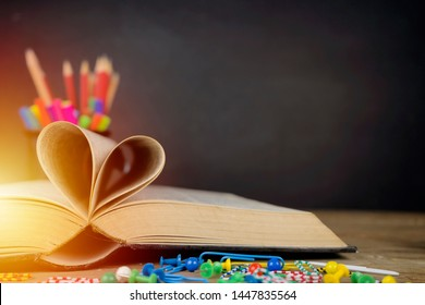 Love story book with open page of literature in heart shape and placed on the table, the background is a blackboard, school study room for national library lovers month and education learning concept.