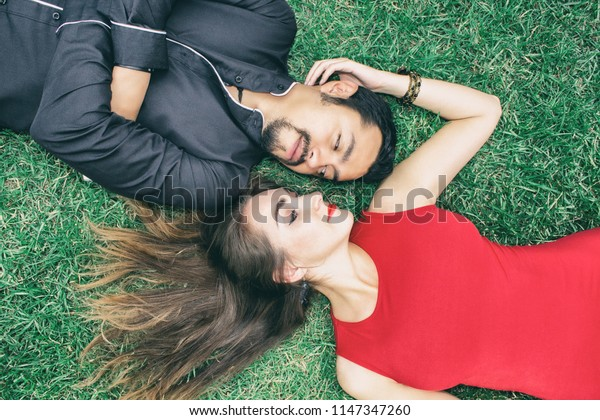 Love story. A brunette man and a beautiful brunette woman lie on the grass.