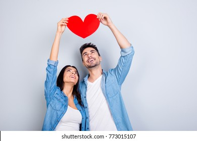 Love story of caucasion beautiful lovely couple in casual outfit, jeans shirt holding, raise up, looking at  red heart together, standing over grey background