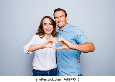 Love story of cheerful, attractive, mature, adult, lovely, cute, sweet couple in casual outfit, jeans, shirt making heart with fingers over grey background