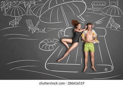 Love story concept of a romantic couple lying on an air mattress against chalk drawings background. Male listening to the music in the headphones and reading a book female trying to gain his attention