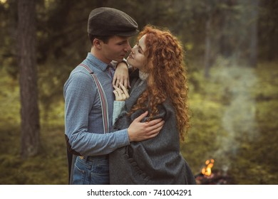 Love story. Couple in forest having fun near bonfire