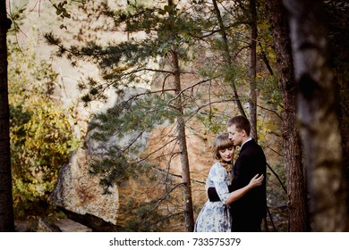 Love story in the forest, near the canyon and water. Bride in designer dress in blue flowers.