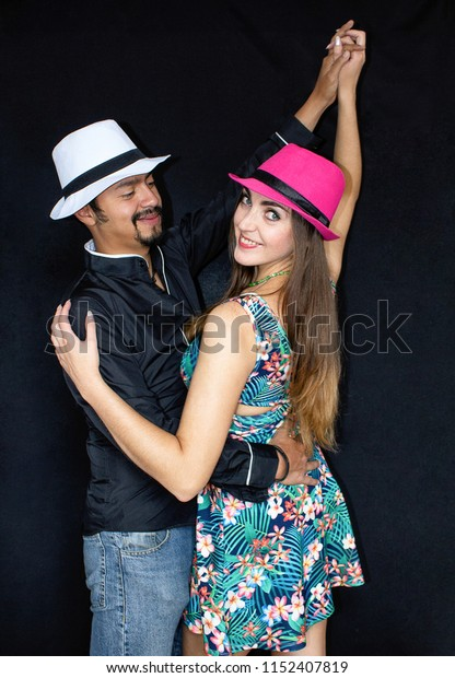 Love story, man and woman brunette in hats dancing on a black background.