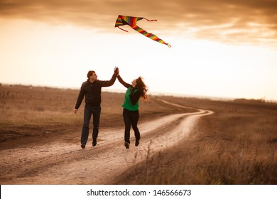 A love story. A man and a woman on autumn road running with a kite. Love and relationships. Autumn sunset.