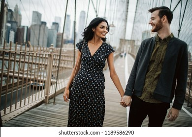 Love story in New York. Man holds woman's hand tender walking around before industrial cityscape of Brooklyn bridge