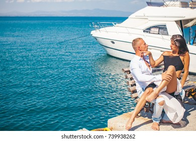 Love story on the sea. Honeymoon. Kiss. Couple in love resting on coastline near the sea in summer. Beautiful young woman holding her boyfriend. Man and woman kissing. Couple in love. Sea beach. Adult