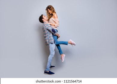 Love story! Profile full body portrait of lovely romantic couple, strong man holding charming woman looking at each other isolated on grey background