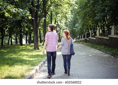 Love story. Summer sunny day, girl and boy walking together in the park.