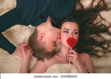 Love story. Young girl, cover their lips with a candy in the form of a heart, her boyfriend gently looks at her girl, the view from the top