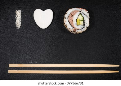 i love sushi written made with rice and one piece of sushi on slate background