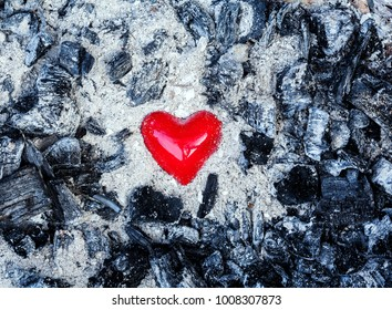 Love symbol red heart on the background of the coal and ashes