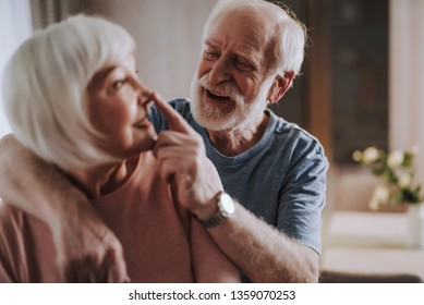 Love and tendance in any age. Close up portrait of happy smiling gray haired male touching nose his beloved female partner while enjoying time together at home