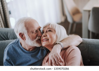 Love and tendance in any age. Close up portrait of happy smiling gray haired man kissing his wife with tender while enjoying time together on sofa