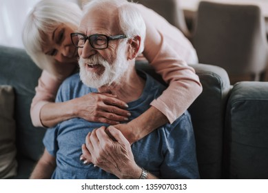 Love and tendance in any age. Close up portrait of happy smiling gray haired woman embracing her man from back while he sitting on sofa at home
