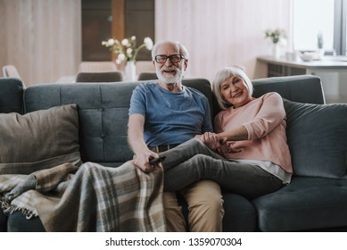 Love and tendance in any age. Front view portrait of happy smiling gray haired man holding legs covering in plaid of her beloved wife while enjoying time together on sofa