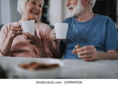 Love and tendance in any age. Waist up cropped head portrait of happy smiling elder man and woman drinking tea with cookies at home