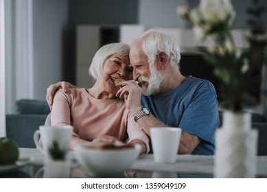 Love and tendance in any age. Waist up portrait of happy smiling elder man feeding his wife with cookies while drinking tea together at home