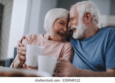 Love and tendance in any age. Waist up portrait of happy elder husband and wife enjoying cozy time together with tea and cookies at home