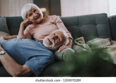 Love and tendance in any age. Waist up portrait of happy smiling gray haired woman and man looking at camera while relaxing on sofa together