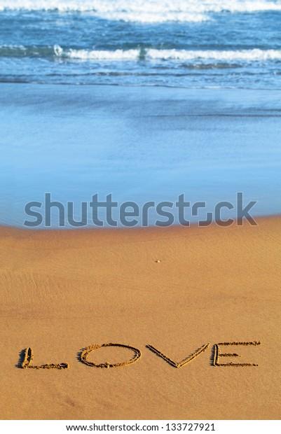 Love text on the beach sand.