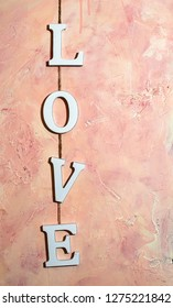 Love text on pink wall at home interior. White wooden charcters L O V E hooked with rope on wall. Concept of love and valentines'd day.