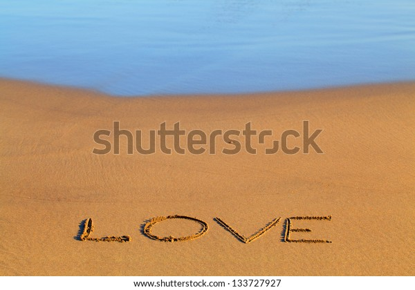 Love text written on the beach sand.
