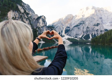 Love to travel and adventure. Woman hiker shows heart sign on background of Dolomites Mountaines. landscape of Braies Lake (Lago di Braies), hiking in alpine lake, Alps, Dolomites, Italy, Europe