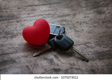 Love travel concept. Red heart and keys car on wooden table. Holiday. Romantic key car.