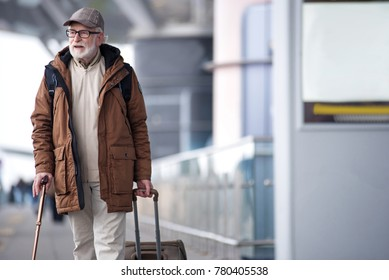 Love traveling. Pleasant bearded gray-haired man with cane is walking along the airport building and carrying suitcase. He is looking aside pensively. Copy space on right side